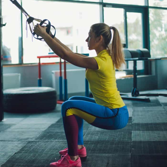 Girl performing TRX Squat