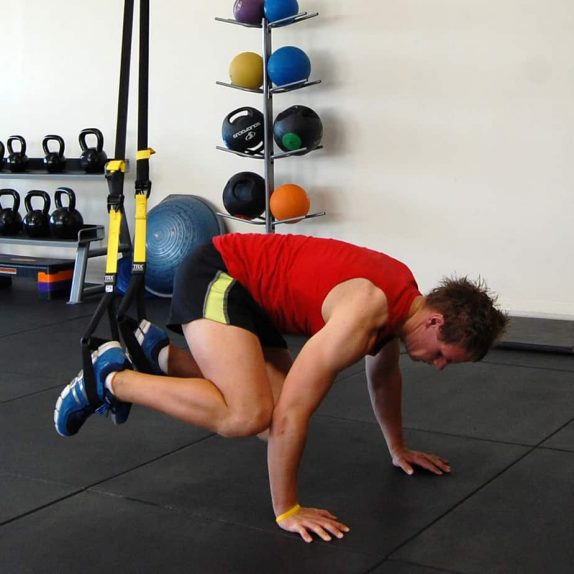 Man performing the TRX atomic push up